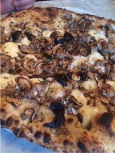 Cremini Mushroom pizza with sweet sausage, garlic, thyme, pecorino, and Gaeta olives