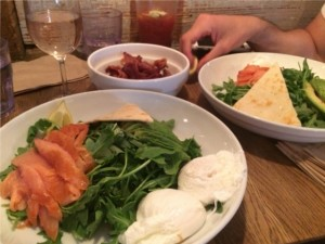 Arugula salad with salmon, poached eggs, and a side of bacon