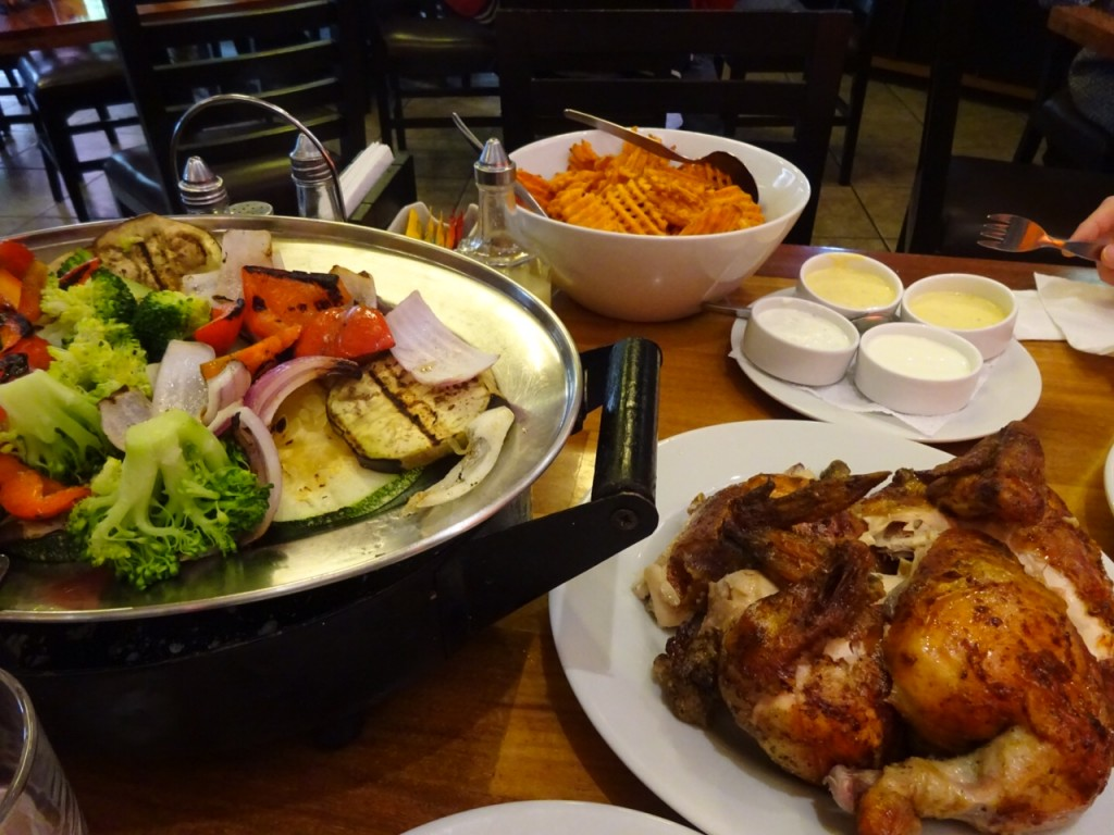 Whole roasted chicken, roasted vegetables, and sweet potato fries at