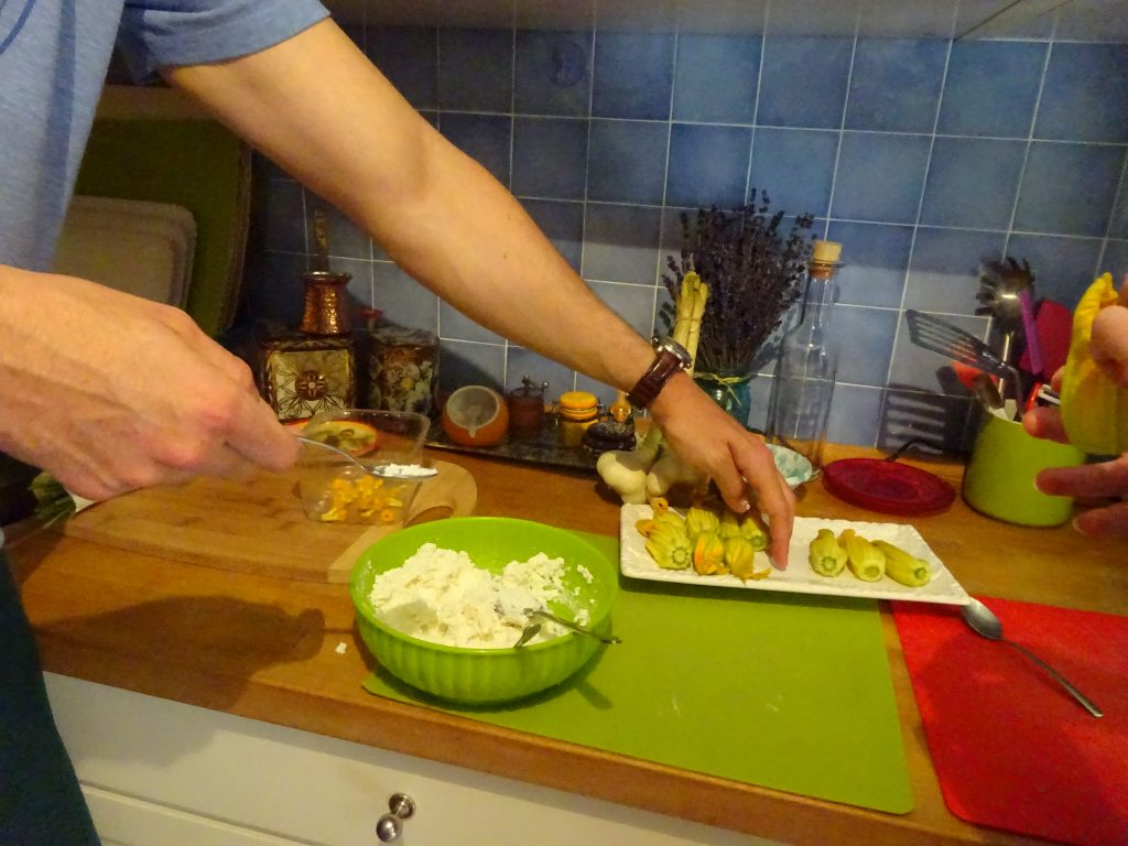 Stuffing zucchini blossoms with ricotta cheese filling